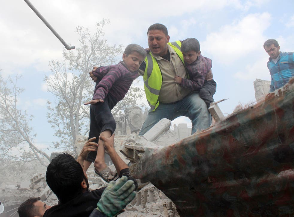Syrian Civil Defence workers evacuate children from a building following a reported airstrike by government forces in a rebel held neighbourhood of the northern Syrian city of Aleppo