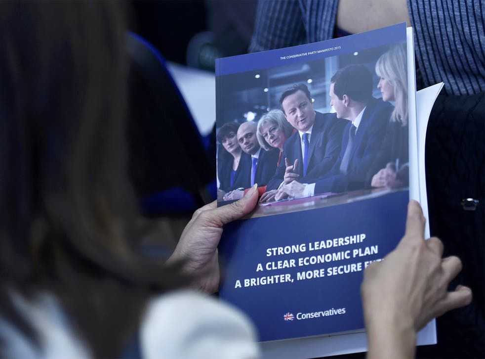 A woman reads the Conservative Party manifesto at its launch in Swindon
