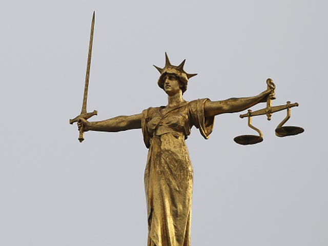 A statue of the scales of justice stands above the Old Bailey
