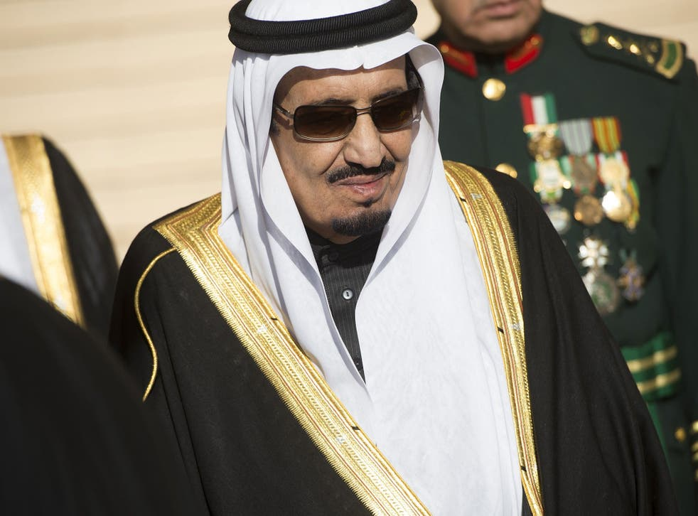 Saudi new King Salman stands during the arrival of US President Barack Obama and First Lady Michelle Obama at King Khalid International Airport in Riyadh on January 27, 2015
