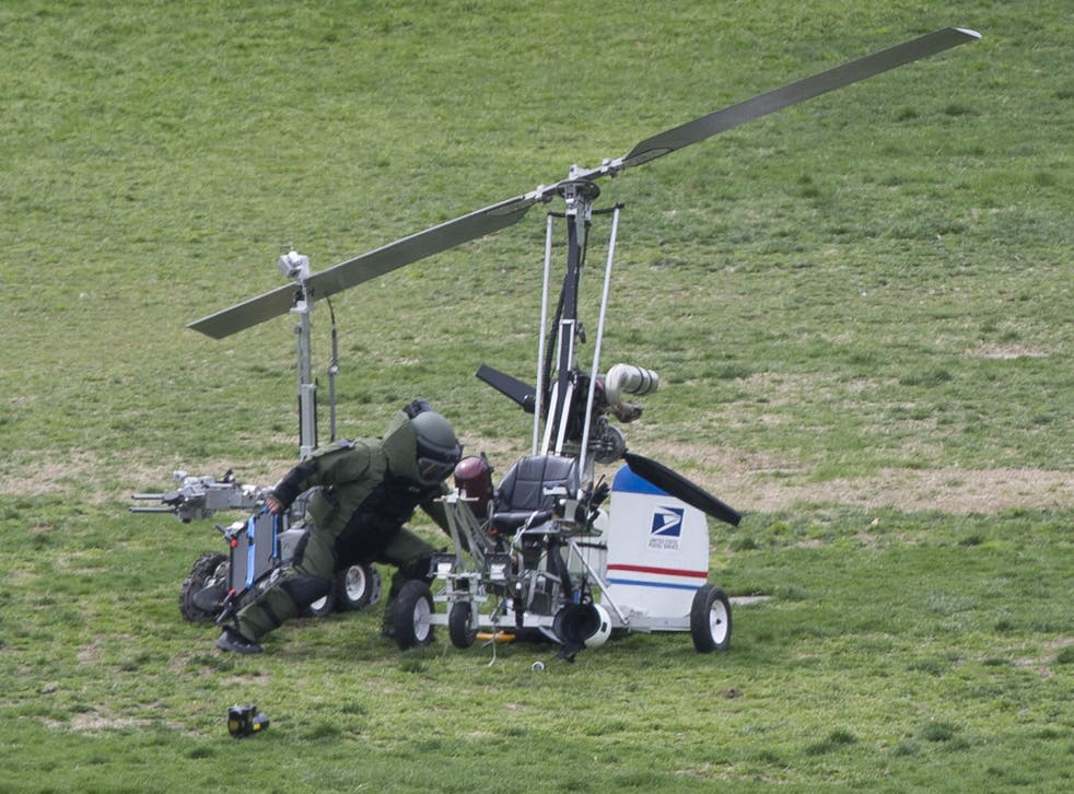 A bomb squad officer inspects the gyrocopter on the Capitol lawn
