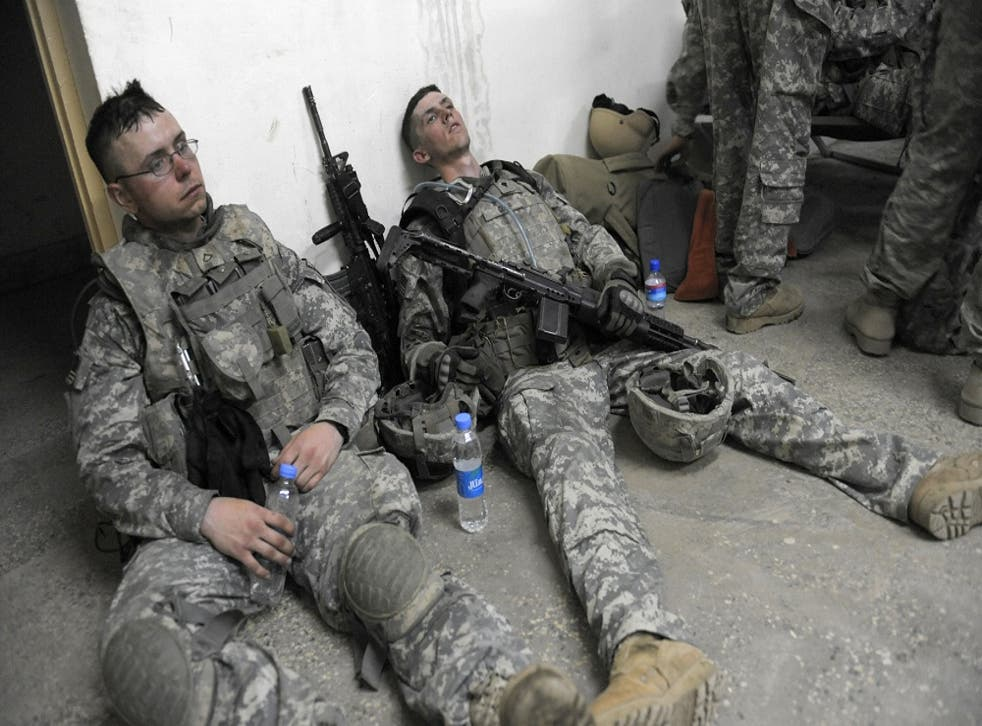 US soldiers from lie exhausted on the floor at an operation post after completing a mission to search for weapons caches in the Alaugal valley in Nishagam,Afghanistan in 2009.