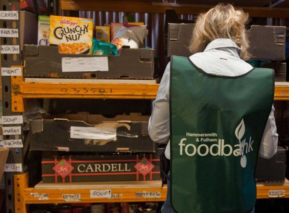 A volunteers sorts through donations of food at the Hammersmith and Fulham food bank run by the Trussell Trust in London