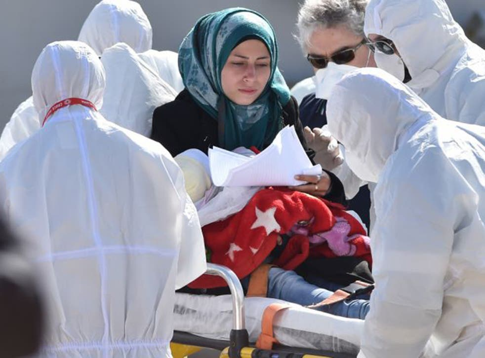 A mother and child receive first aid as they disembark in Italy on Saturday