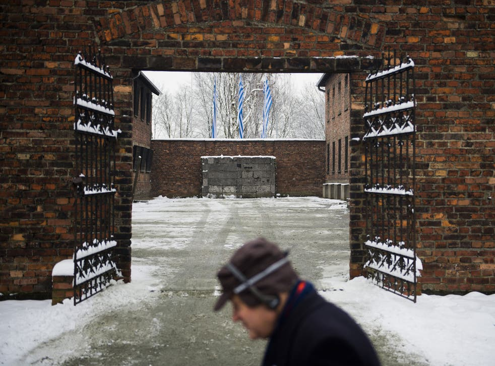 A visitor walks past the gates with the 'death wall' behind it in the former Auschwitz concentration camp held by the Nazis in Oswiecim