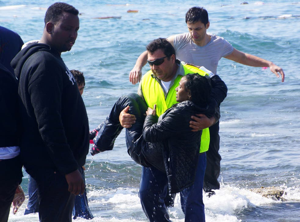 A man rescues a migrant from the Aegean sea, in the eastern island of Rhodes, on Monday