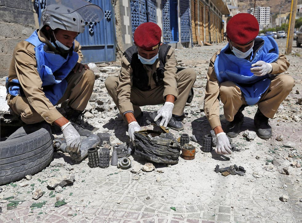 Yemeni soldiers collect mines and explosives at the scene of an airstrike allegedly carried out by the Saudi-led coalition on a nearby Houthi-controlled missile depot in Sanaa