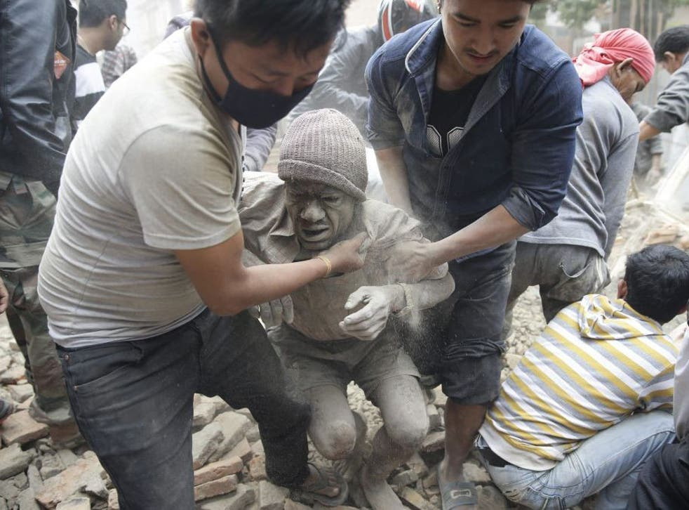 People free a man from the rubble of a destroyed building after an earthquake hit Nepal, in Kathmandu, Nepal