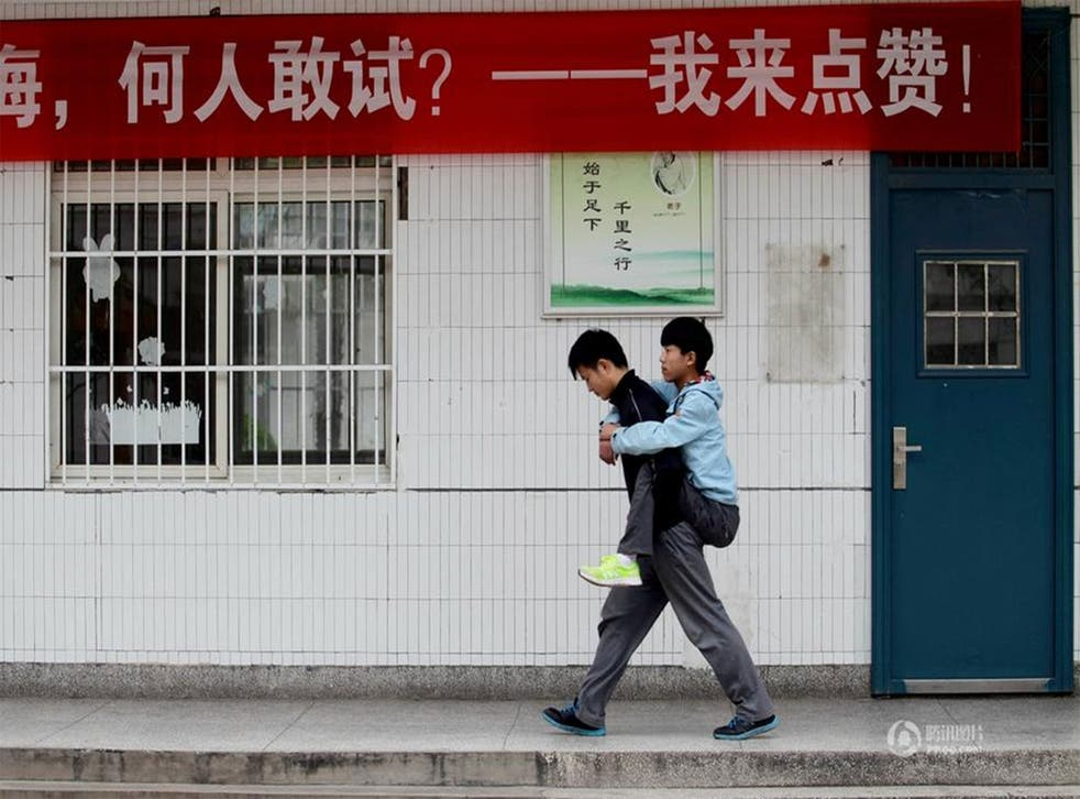 Images posted to Weibo showed 18-year-old Xie Xu giving his disabled friend Zhang Chi lifts to school