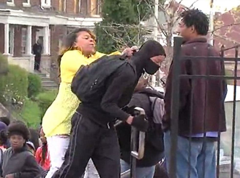 A woman reprimands a young man believed to be her son for allegedly attempting to take part in the riots