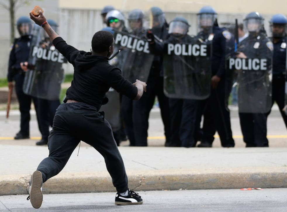 A man throws a brick at police, following the funeral of Freddie Gray in Baltimore
