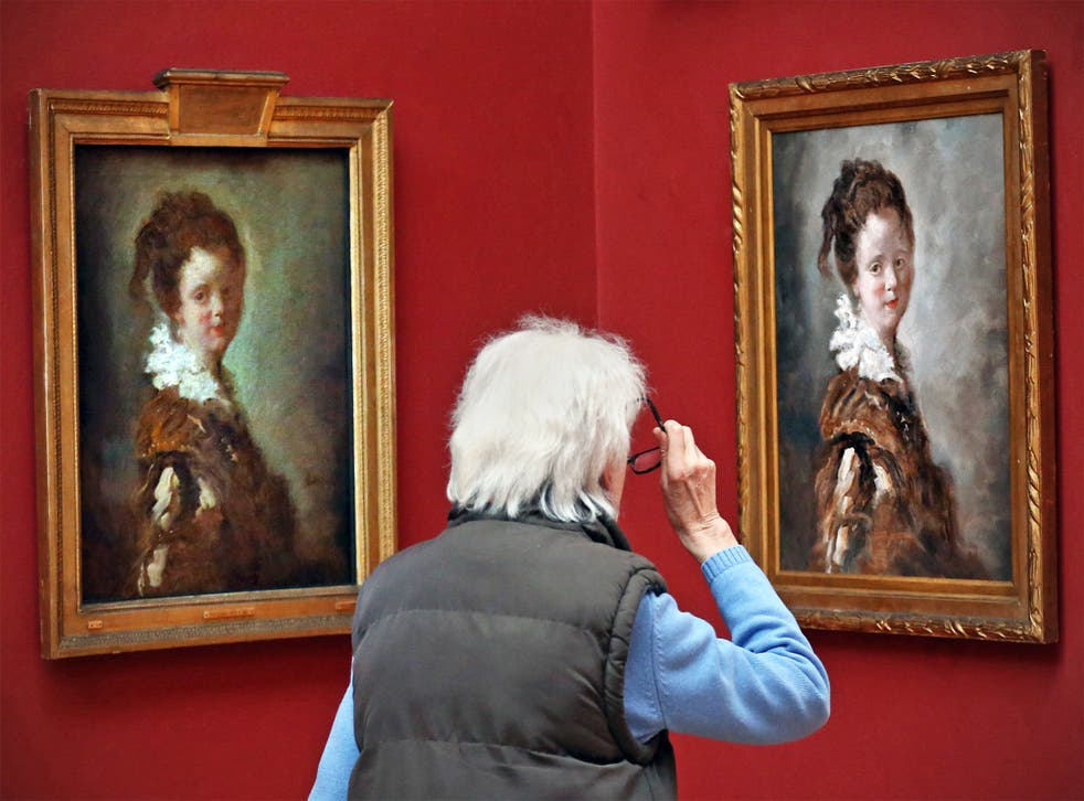 A visitor takes a close look at Jean-Honore Fragonard's 'Young Woman' and its replica (on right)
