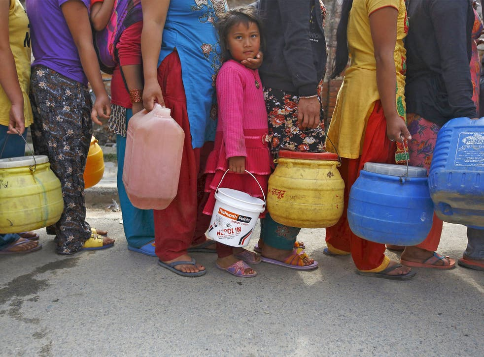 A girl stands in a queue to fill her container with water near the makeshift shelters in Kathmandu