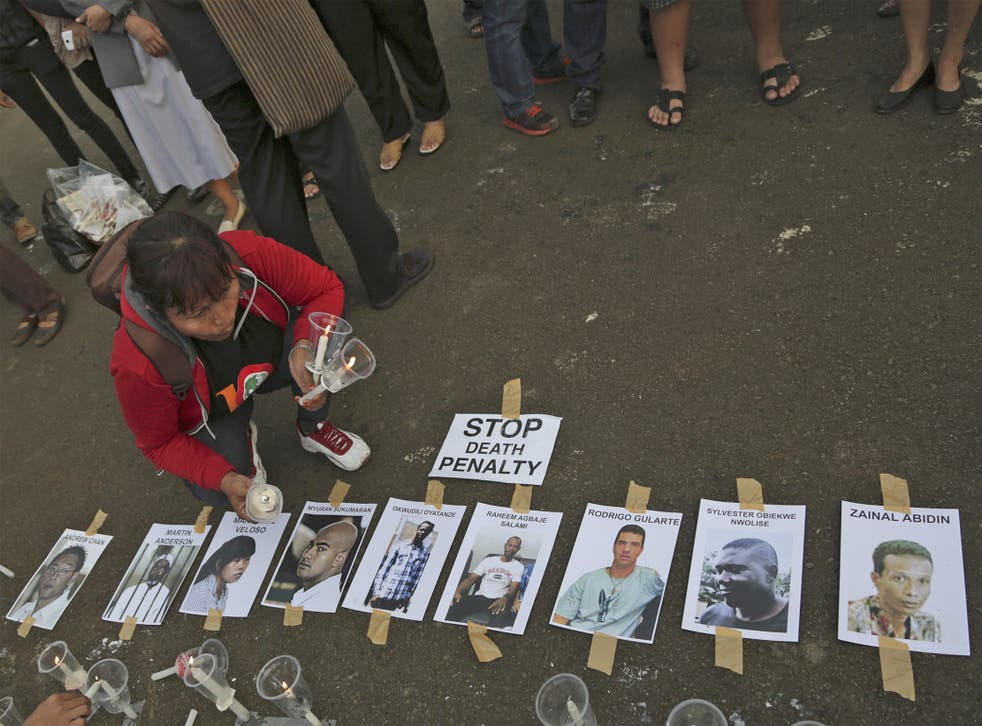 An activist holds candles near portraits of the 'Bali Nine' in Jakarta, Indonesia