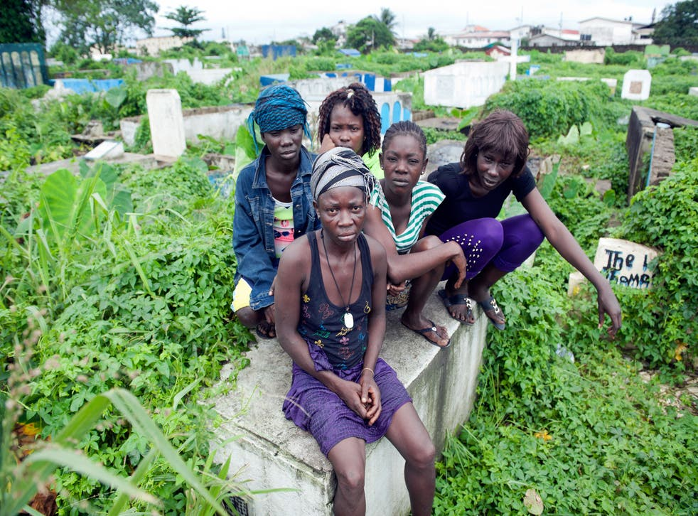 A group of female tomb dwellers sit on top of their make-shift home in Monrovia, Liberia