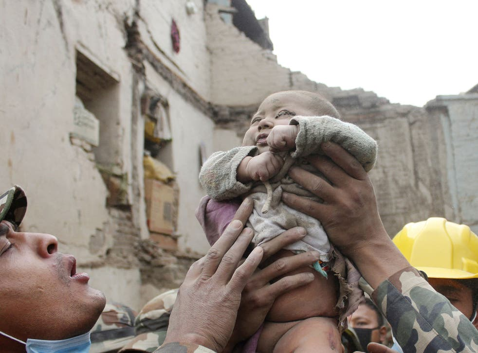 Four-month-old baby boy Sonit Awal is held up by Nepalese Army soldiers after being rescued from the rubble of his house in Bhaktapur, Nepal
