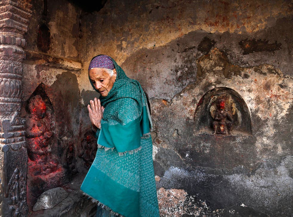 An elderly woman prays at a temple in Kathmandu damaged by the earthquake