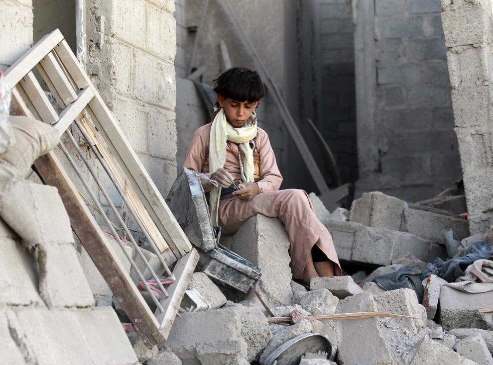 A Yemeni boys sits on the rubble of houses destroyed by an overnight Saudi-led air strike on a residential area in Yemen's capital, Sana