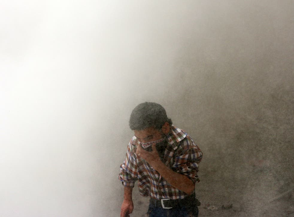 A man protects himself from dust following a reported barrel bomb attack by Syrian pro-government forces in Aleppo