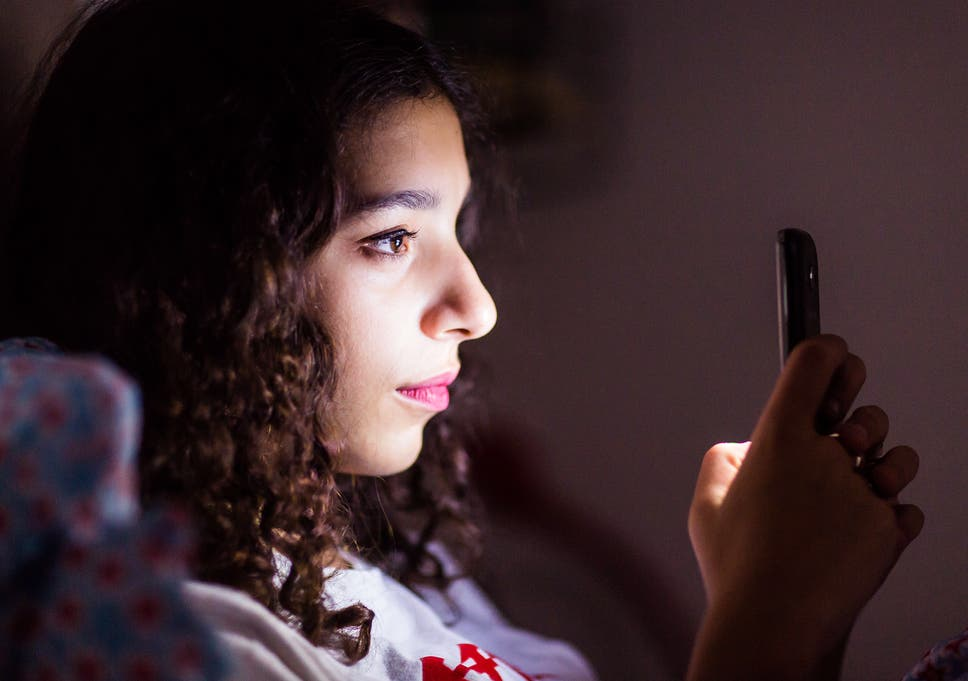 A teenage girl uses her smartphone in bed.
