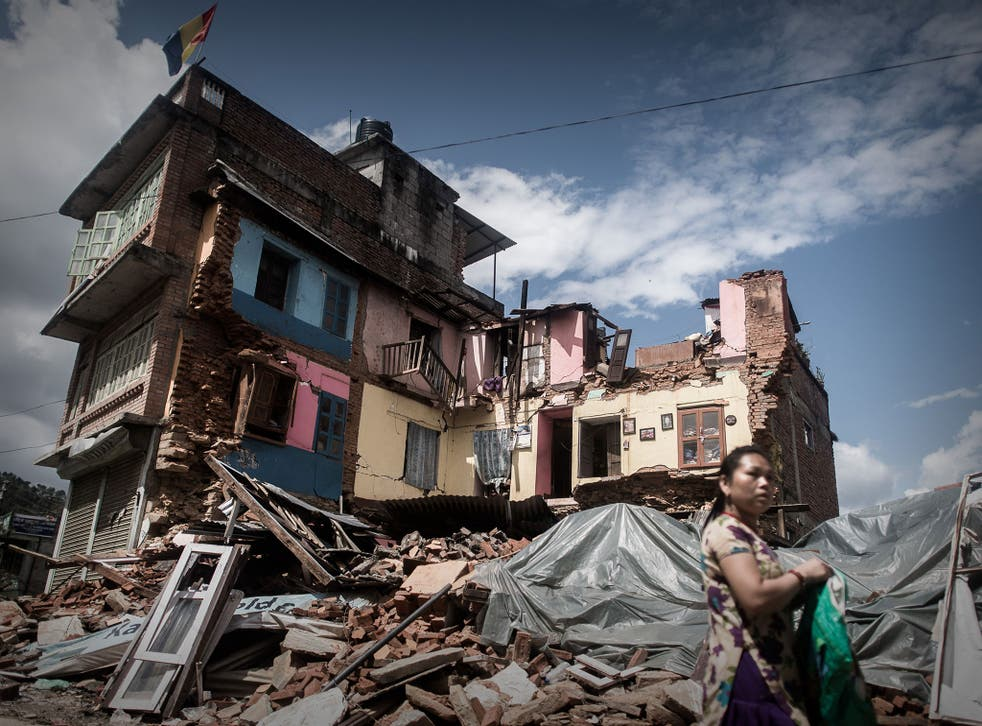 An earthquake survivor passes a destroyed house in Chautara, about 50 miles from Kathmandu in the central Sindhupalchok district, one of the worst-hit areas