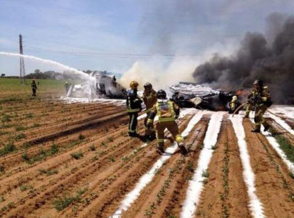 Firemen trying to extinguish the flames after a Airbus A400 military plane crashed near Seville on 9 May