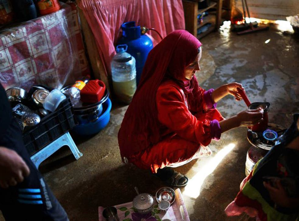 A woman from the city of Homs makes coffee in her makeshift tent home