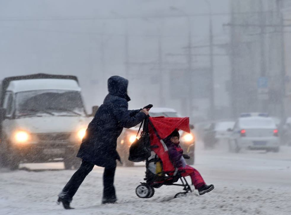 Women pushes pram in Moscow town