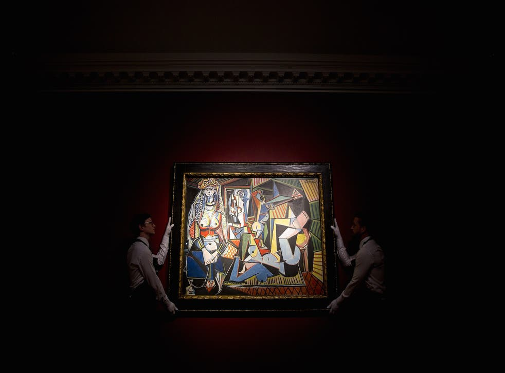 Christie's staff hold up Picasso's  Les femmes d'Alger (version O) ahead of the auction