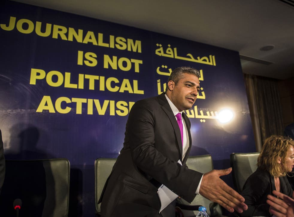 Egyptian-Canadian journalist Mohamed Fahmy, formerly with Al-Jazeera, is greeted by an unknown man duting a press conference in Cairo on May 11, 2015. Fahmy, who was sentenced last year to up to 10 years in prison, has sued his Qatari employer for $100 mi