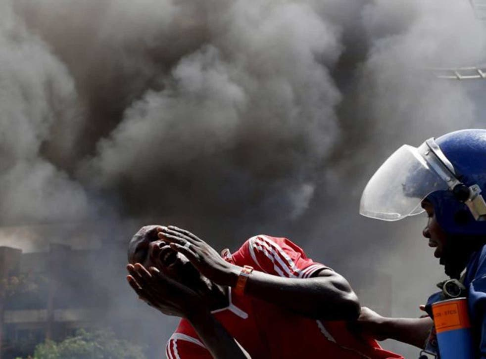 A man screams in the street as an Burundi police officer attempts to detain him