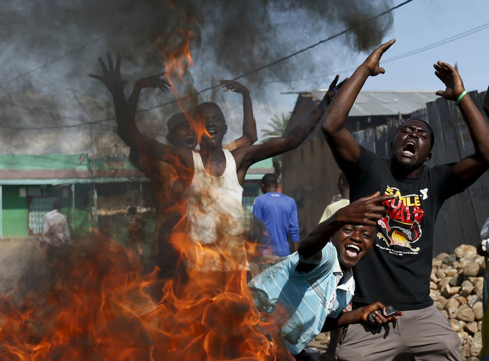 Protesters, who are opposed to President Pierre Nkurunziza's decision to run for a third term, gesture in front of a burning barricade in Bujumbura, Burundi