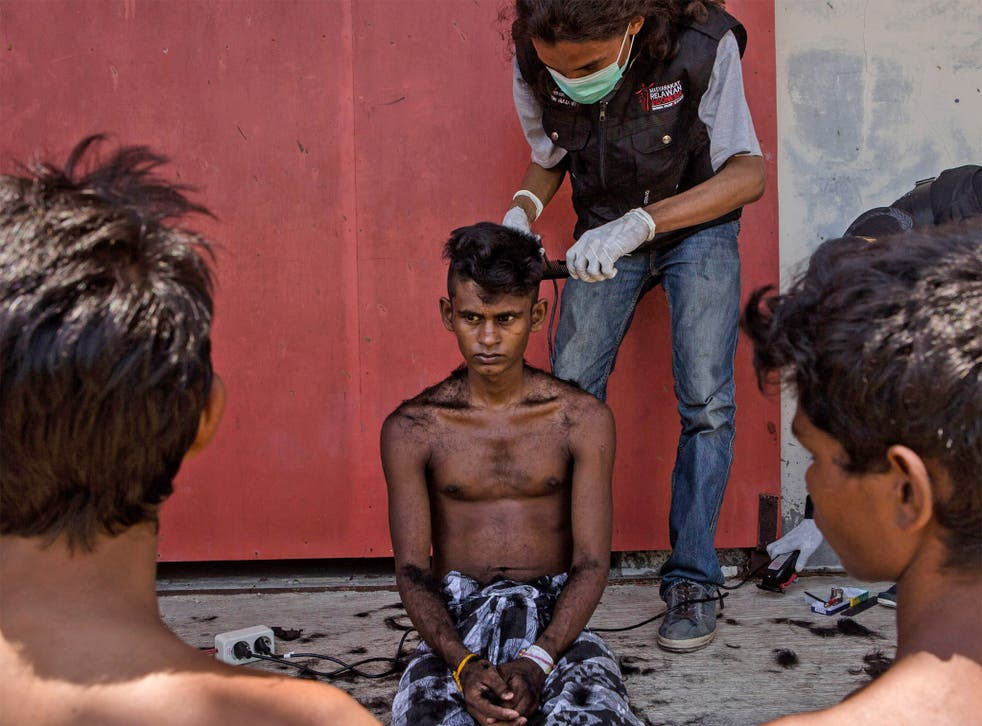 A volunteer cuts the hair of a Rohingya migrant at a temporary shelter in Kuala Langsa, Indonesia