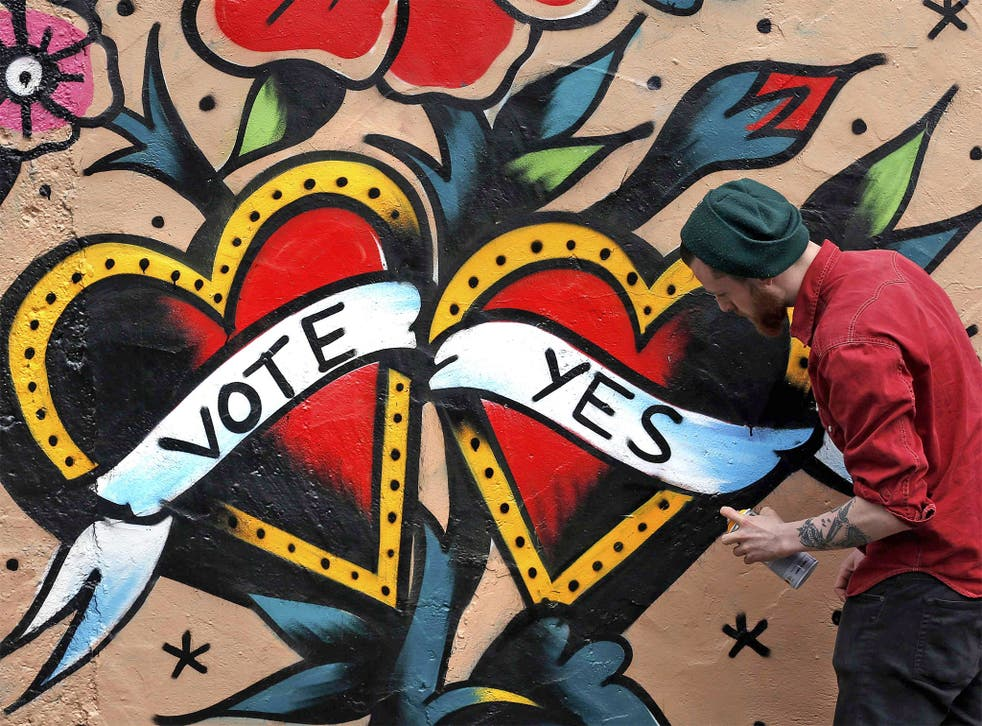 A graffiti artist finishes a Yes campaign piece in central Dublin