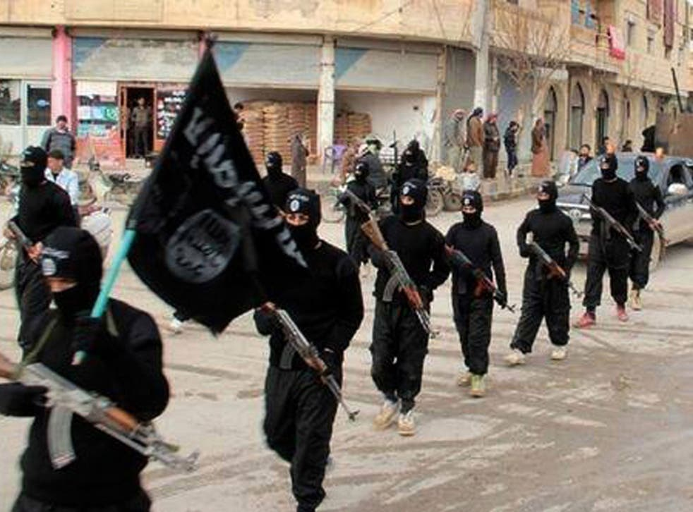 Masked Isis fighters march through the Syrian city of Raqqa