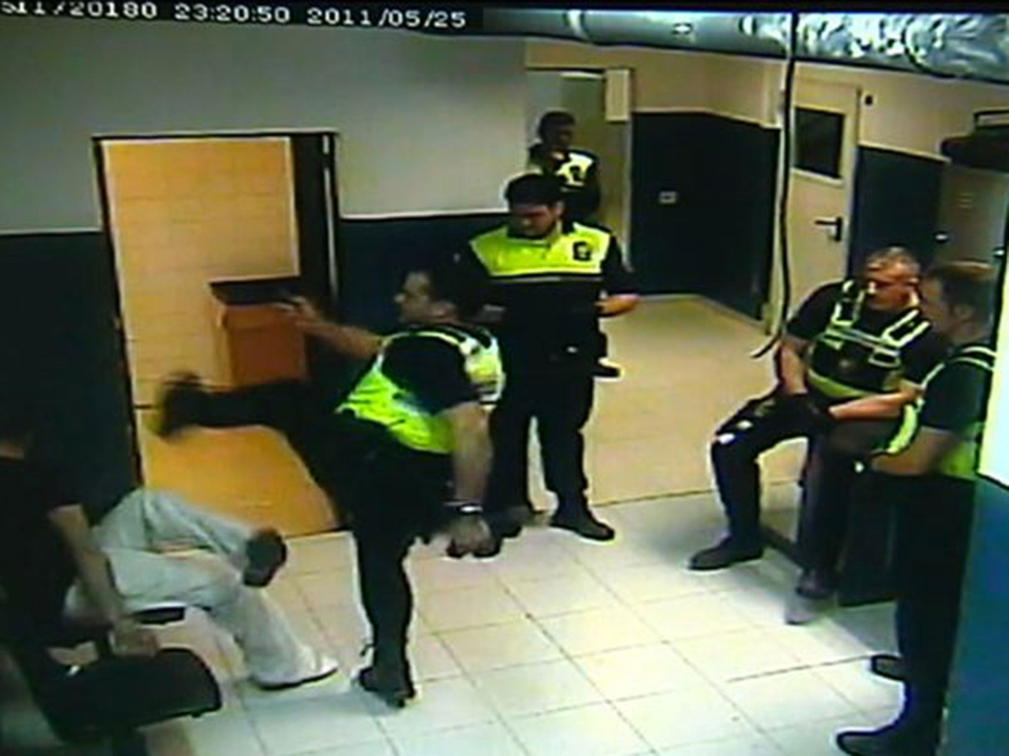 Spanish policeman filmed 'karate kicking' handcuffed suspect twice in newly released video