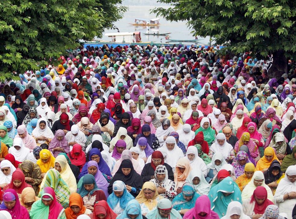 Kashmiri Muslim women pray together outdoors