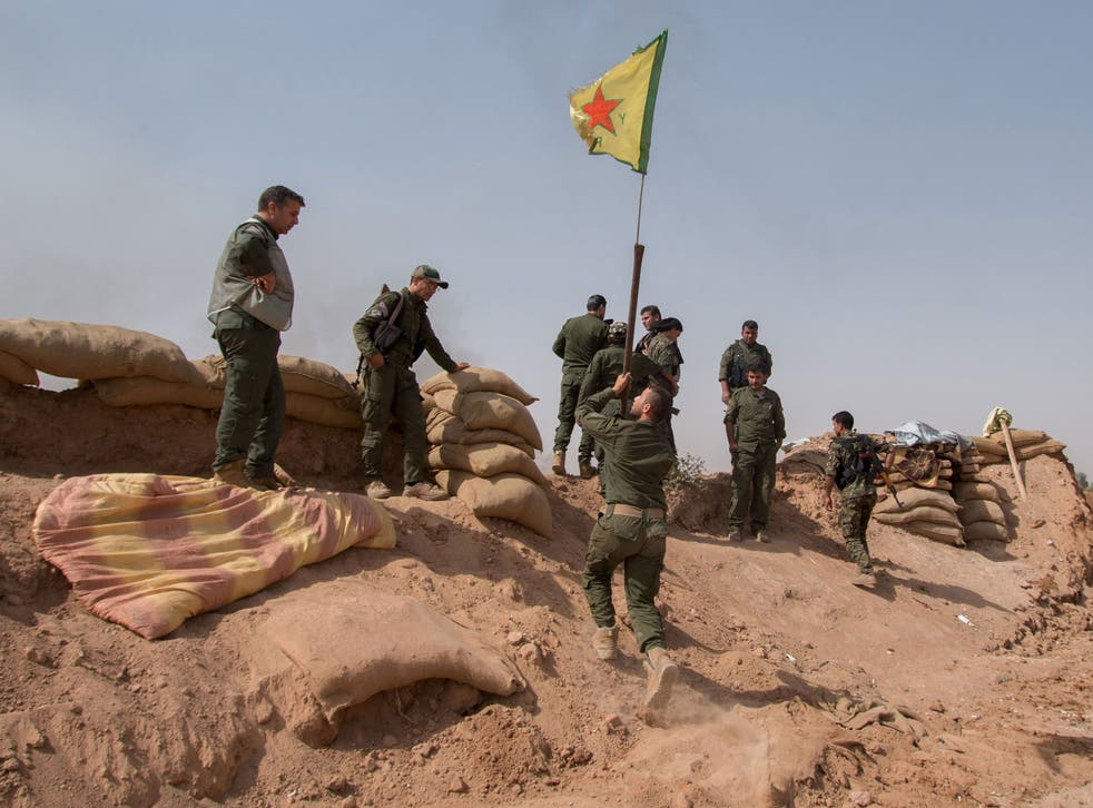A Kurdish People's Protection Units (YPG) flag is raised in a village near Mount Abdulaziz on Thursday, after retaking the territory from Isis