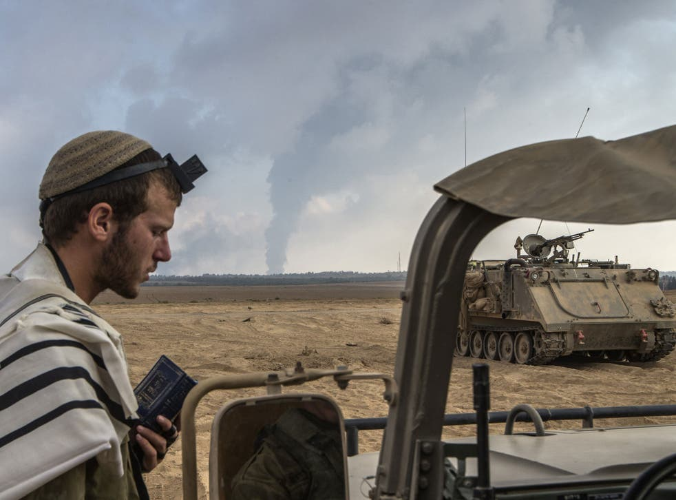 An Israeli soldier prays on the Israeli side of the border with the Gaza Strip, on July 29, 2014, as smoke billows from a power plant following overnight Israeli shelling in the coastal Palestinian enclave.