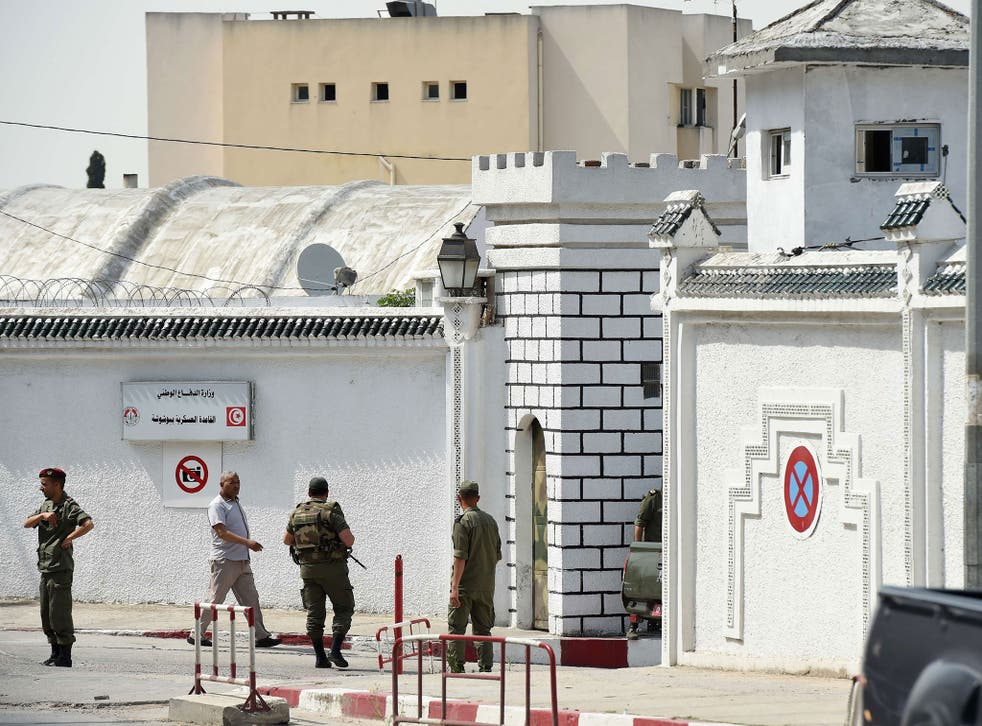 Tunisian soldiers stand guard outside the Bouchoucha army barracks in Tunis on May 25, 2015 after a soldier opened fire at his colleagues