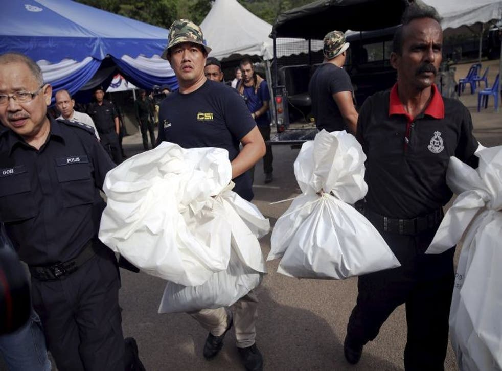 Forensic policemen carry body bags with human remains
