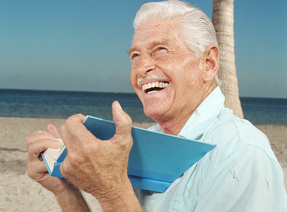 A senior white man reading on the beach, laughing.
