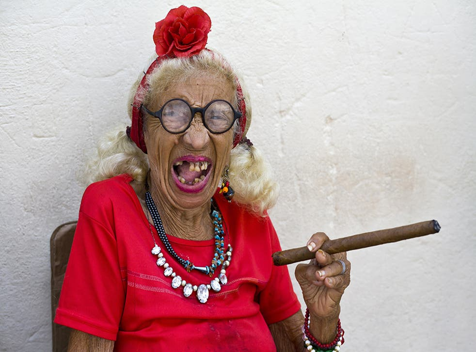 An old woman smoking a cigar in Cuba and loving life