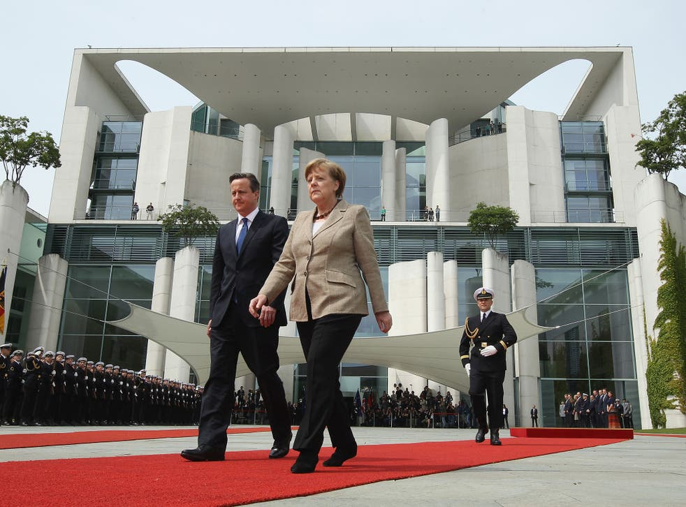Almost in step, Angela Merkel and David Cameron prepare to review a guard of honour in Berlin yesterday