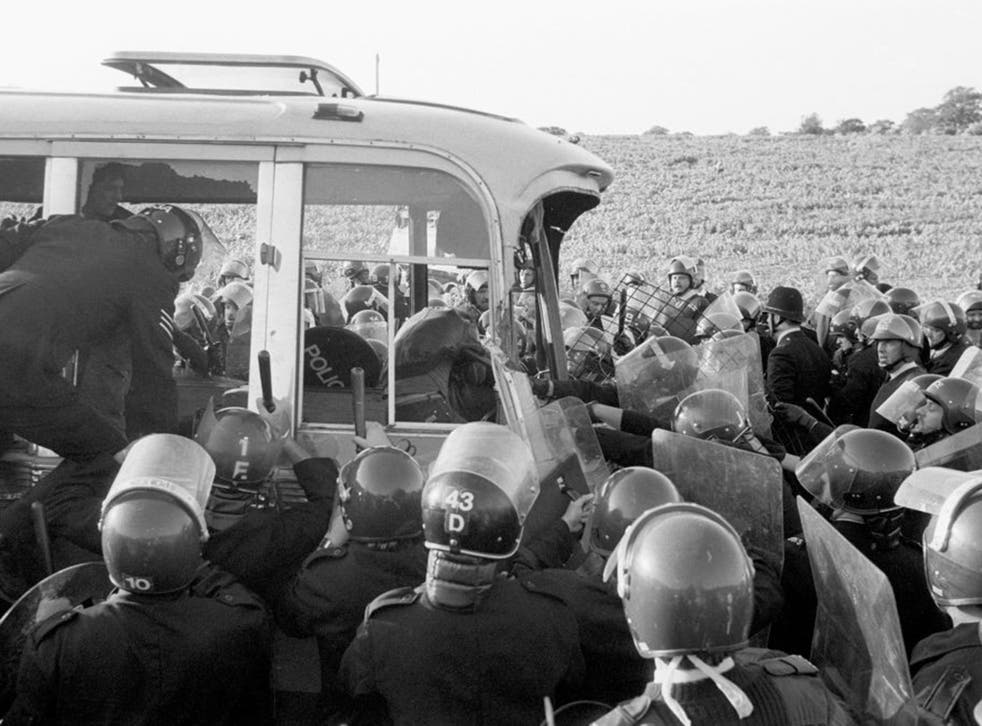 Stonehenge Protest. An army of police surround the last coach to be stopped from racing round the field near Stonehenge where violence erupted this evening.