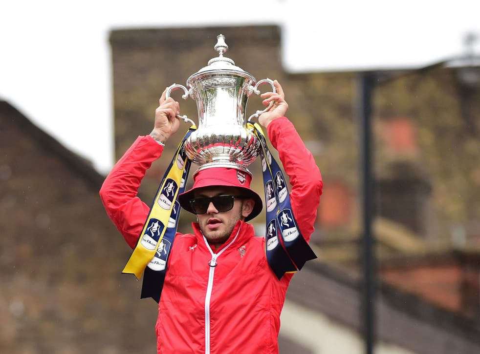 Jack Wilshere puts the trophy on his head