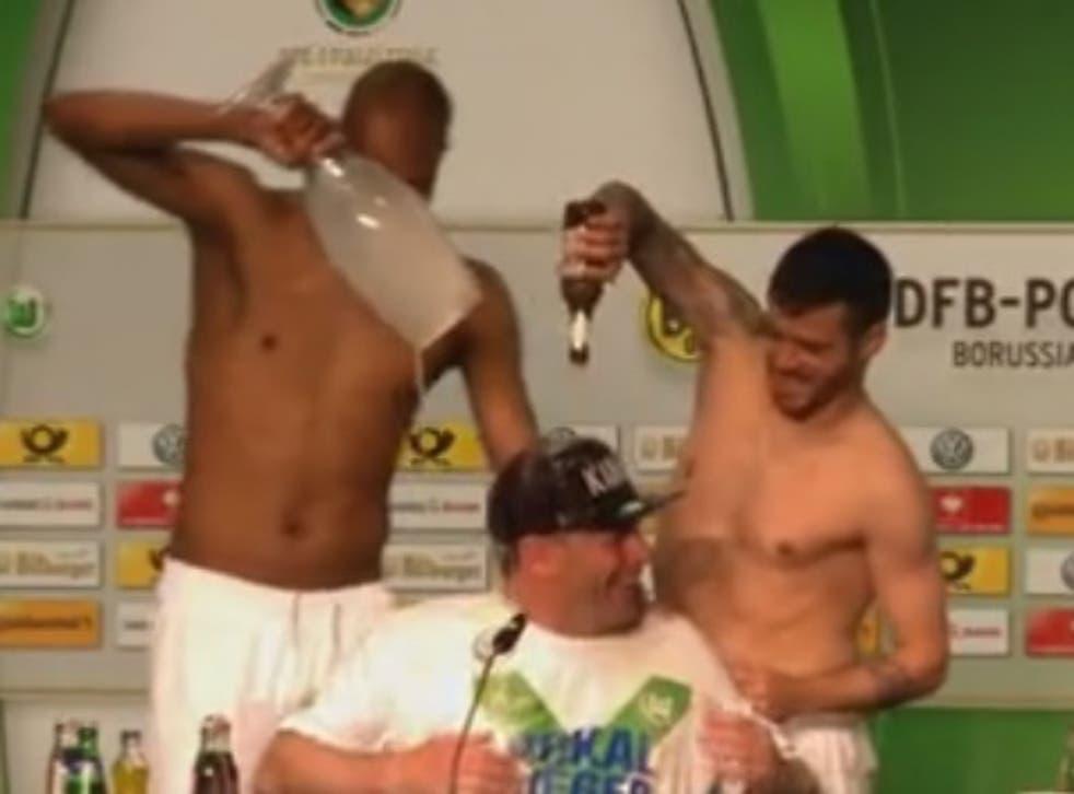Naldo and Vieirinha give manager a beer-shower.