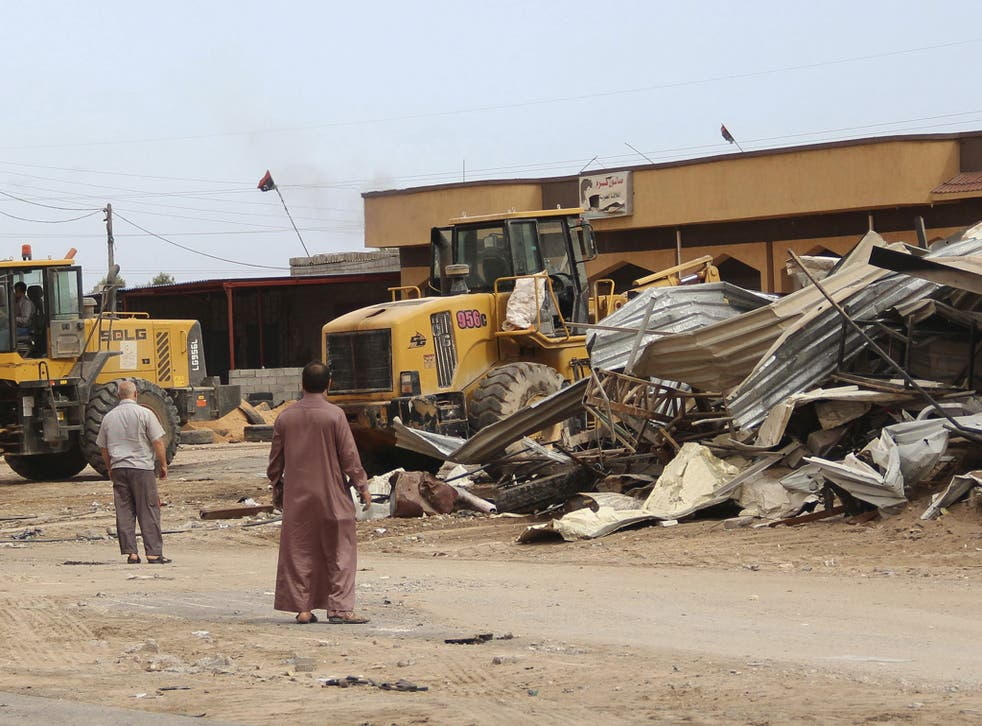Men watch as bulldozers remove debris in front of a damaged building after a suicide car bomber blew himself up at a checkpoint in Dafniya outside Mistrata, Libya
