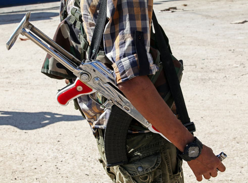 A fighter with the Kurdish People's Protection Units stands in the streets of Kobane