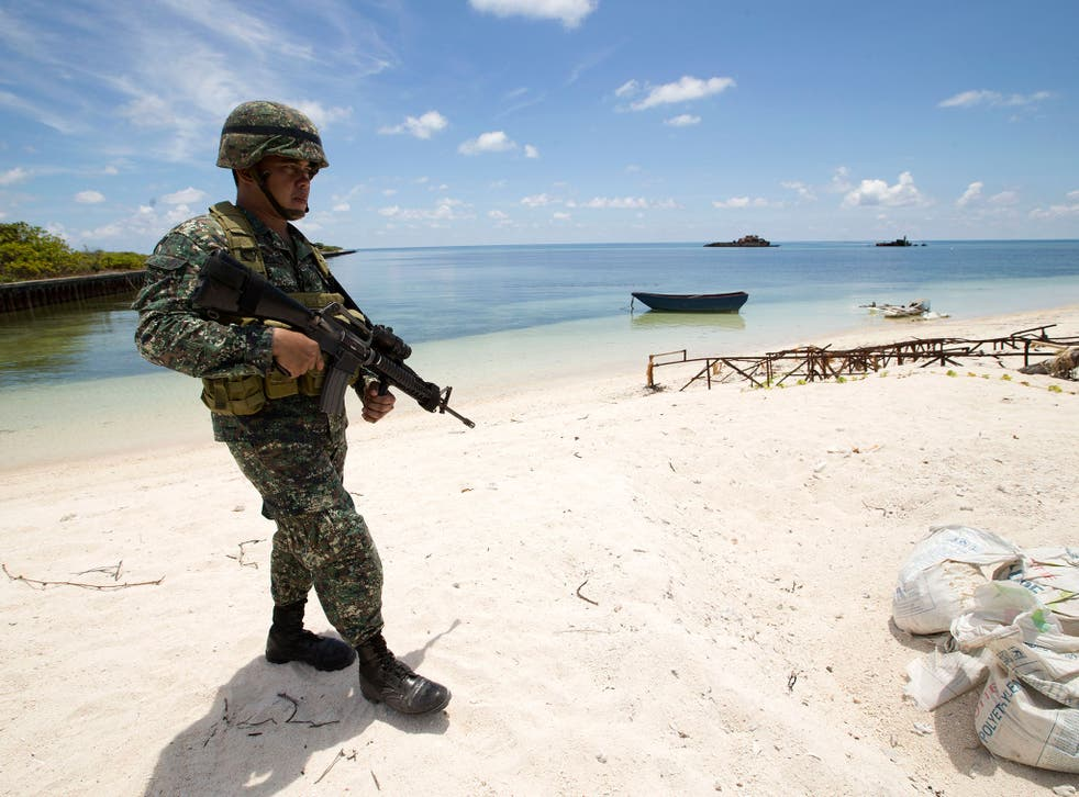 A Filipino soldier on patrol on Pagasa, one of the Spratly Islands. Tension in the region is growing because of China's alleged plans to station military aircraft on some of the islands